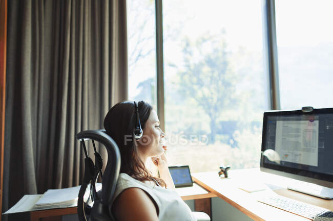 Businesswoman with headset working at computer in sunny home office — Stock Photo