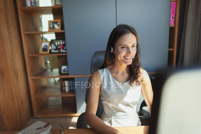 Smiling businesswoman with headset working at computer in home office — Stock Photo