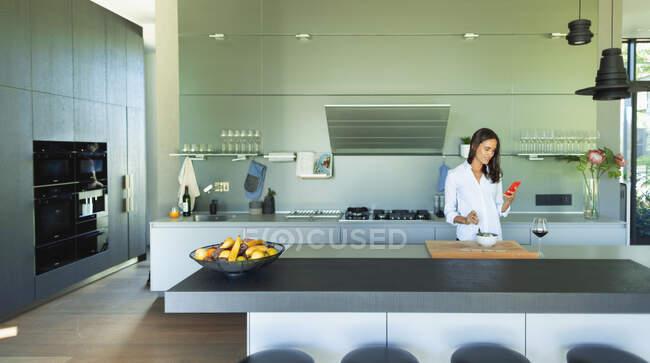 Donna con smart phone mangiare in cucina moderna — Foto stock