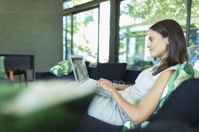 Geschäftsfrau arbeitet von zu Hause aus mit Laptop auf Wohnzimmersofa — Stockfoto