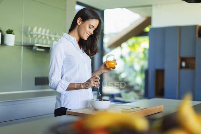 Кузнечиха пьет сок и ест фрукты на кухне — стоковое фото