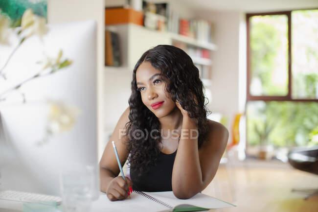 Молода жінка працює за комп