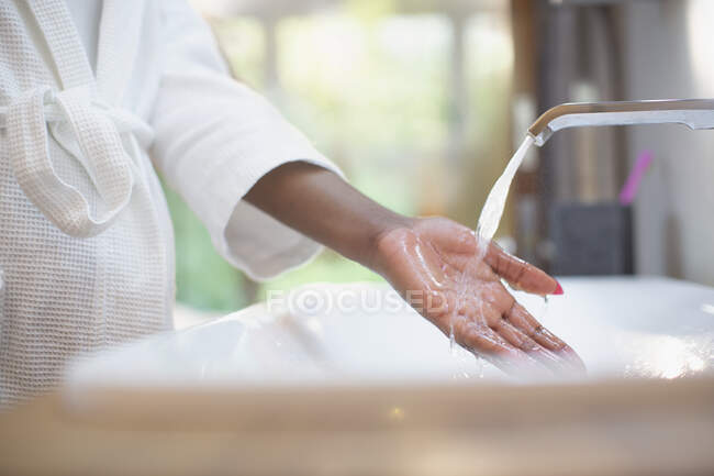 Woman with hand under bathroom water faucet — Stock Photo