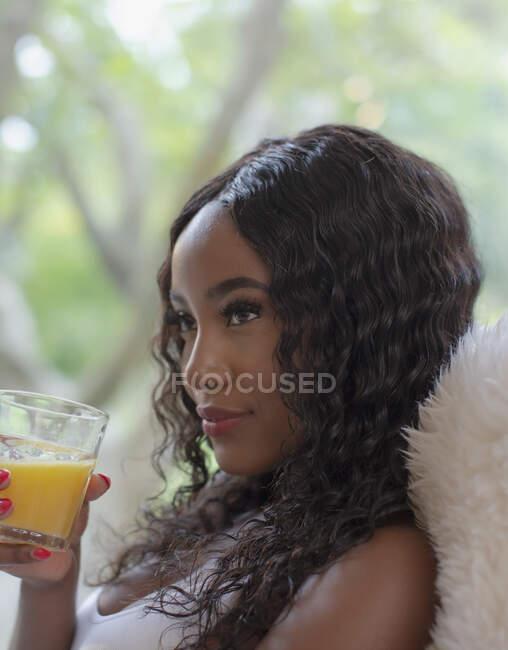 Молодая женщина пьет апельсиновый сок — стоковое фото