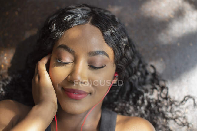 Serene young woman listening to music with headphones — Stock Photo