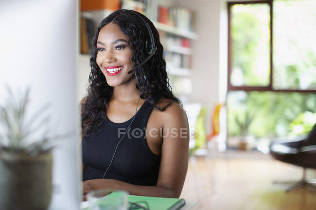 Happy young woman with headset working at computer in home office — Stock Photo