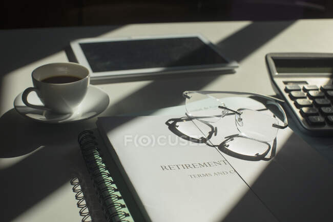 Retirement portfolio on sunny desk with coffee and eyeglasses — Stock Photo