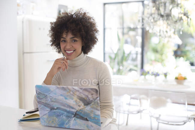 Portrait happy young woman working at laptop in kitchen — Stock Photo