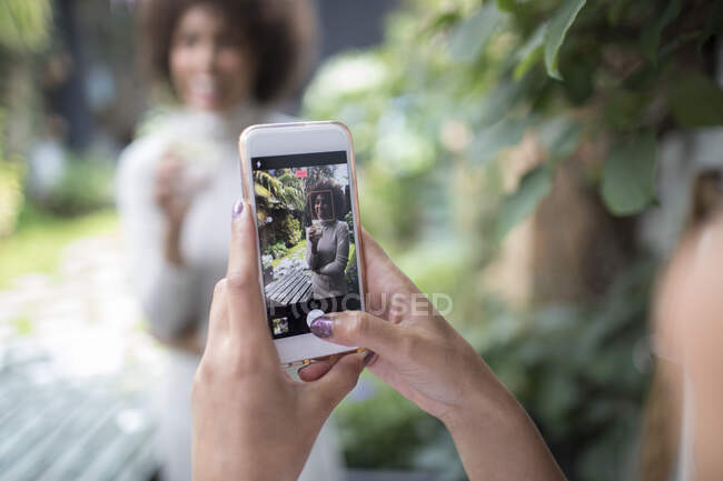 Personal perspective woman with smart phone photographing friend — Stock Photo