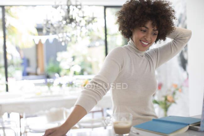Feliz jovem freelancer feminino trabalhando na cozinha — Fotografia de Stock