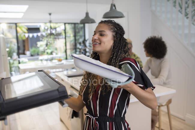 Junge Frau kocht offene Ofentür in Küche — Stockfoto