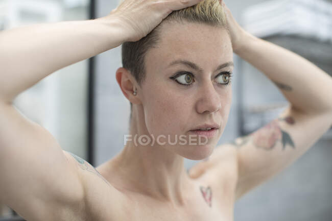 Close up donna con tatuaggi e mani in capelli — Foto stock
