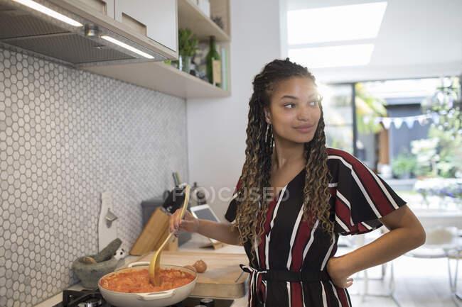 Молодая женщина готовила на плите на кухне — стоковое фото