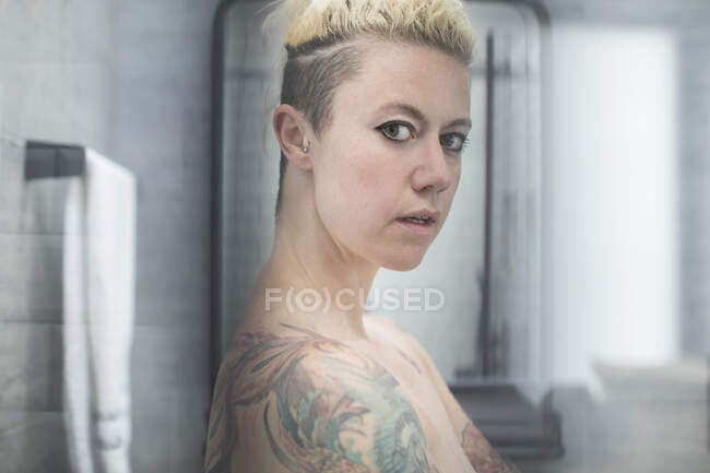Portrait confident woman with tattoos and bare shoulders in bathroom — Stock Photo