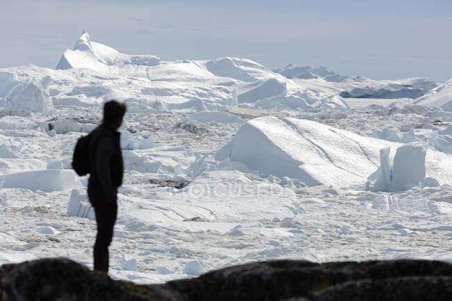 Silhueta de homem olhando ensolarado gelo glacial derreter Groenlândia — Fotografia de Stock