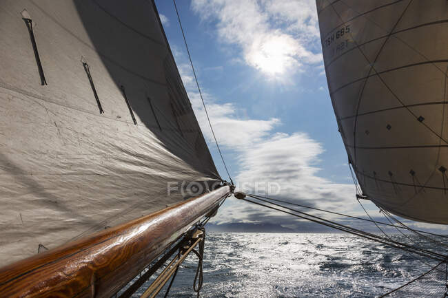 Sail and wooden sailboat mast over sunny tranquil Atlantic Ocean — Stock Photo