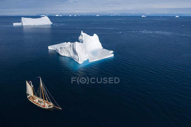 Navio que navega através de icebergs no oceano azul ensolarado Groenlândia — Fotografia de Stock
