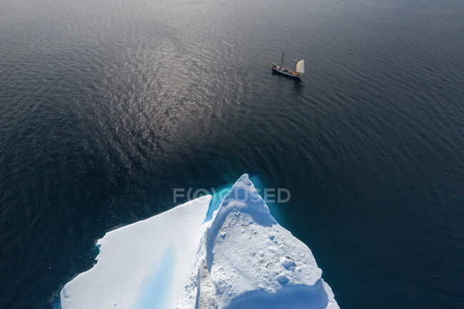 Drone point of view ship sailing past iceberg on sunny ocean Greenland — Stock Photo
