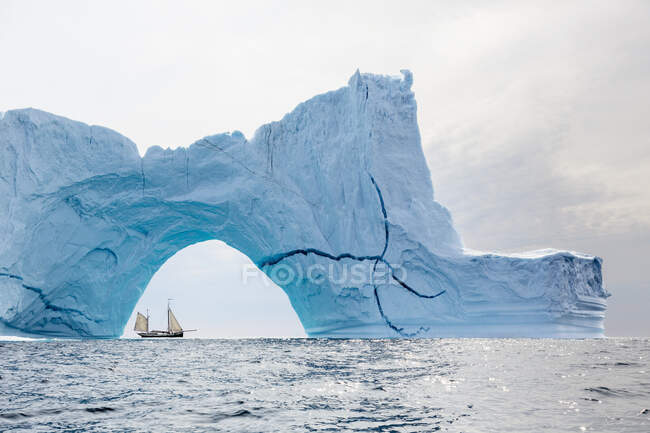 Ship sailing behind majestic iceberg arch on Atlantic Ocean Greenland — Stock Photo