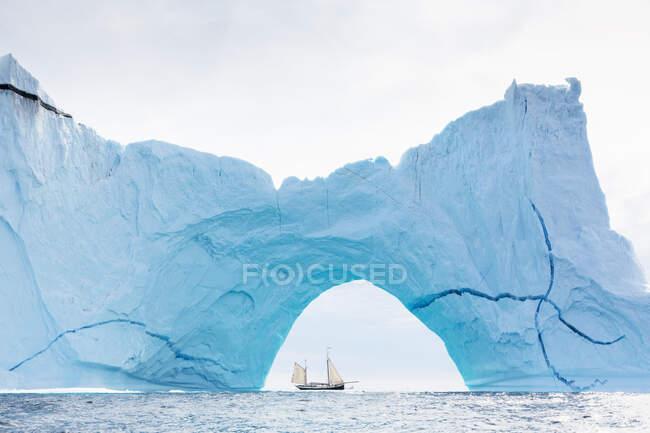 Корабль, плывущий за величественной айсбергской аркой на Атлантическом океане — стоковое фото