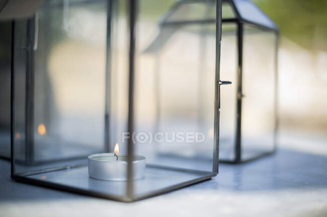 Close up tea light candle in clear glass lantern — Stock Photo