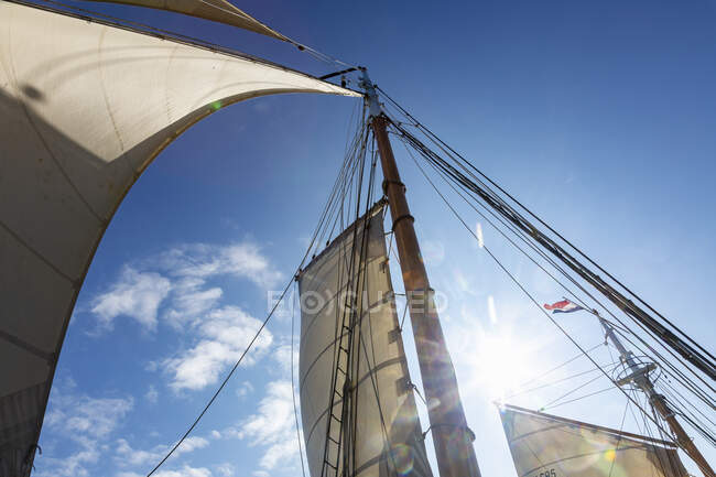 Wooden and mast and sailboat sails below sunny blue sky — Stock Photo