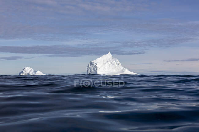 Majestic iceberg formations over sunny blue ocean — Stock Photo