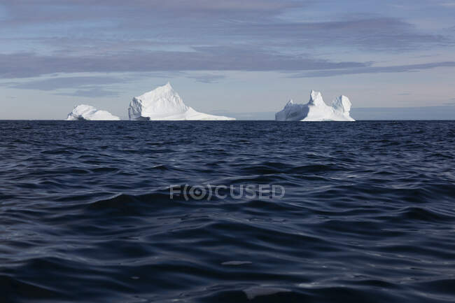 Majestosos icebergs sobre azul ensolarado Oceano Atlântico Groenlândia — Fotografia de Stock