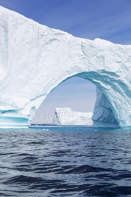 Majestic iceberg arch over sunny blue Atlantic Ocean Greenland — Stock Photo