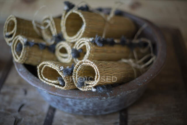 Rolled up rustic straw placemats in bowl — Stock Photo