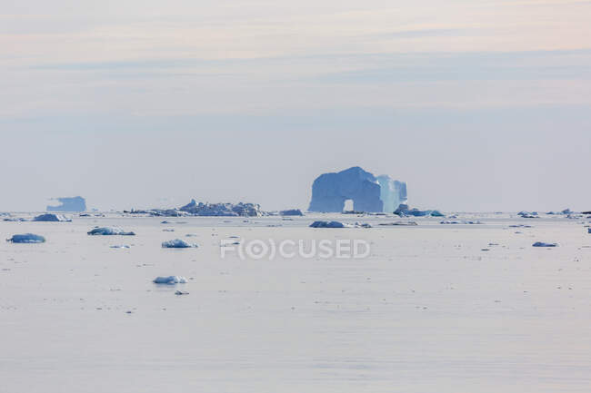 Majestoso arco de iceberg distante no tranquilo Oceano Atlântico Groenlândia — Fotografia de Stock