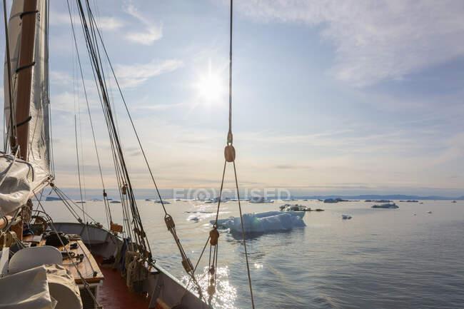 Корабль, плавающий среди тающего полярного льда на солнечном Атлантическом океане Гренландия — стоковое фото