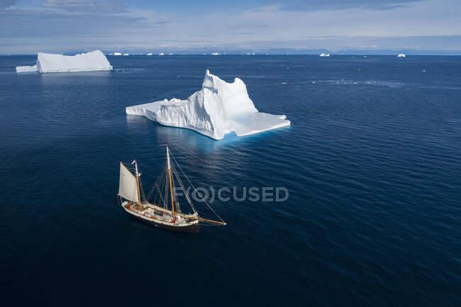 Navio que navega através de majestosos icebergs em azul ensolarado Oceano Atlântico Groenlândia — Fotografia de Stock