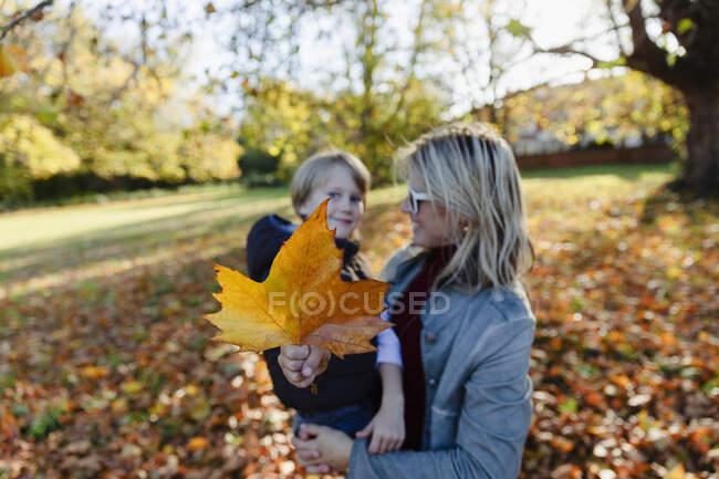 Retrato mãe e filho com folha de outono no parque ensolarado — Fotografia de Stock