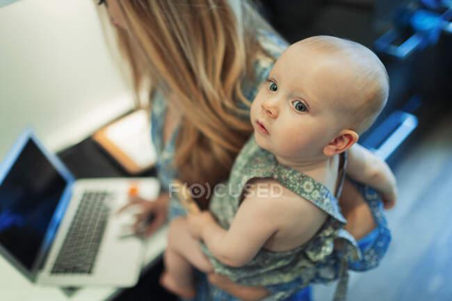 Мама працює за ноутбуком і тримає милу донечку. — стокове фото