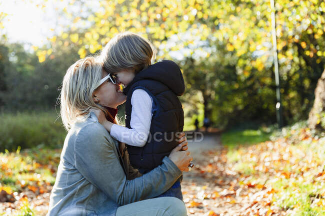Affectionate mother and son hugging in sunny autumn park — Stock Photo