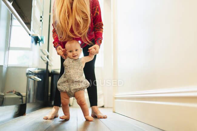 Portrait mother helping baby daughter walk in corridor — Stock Photo