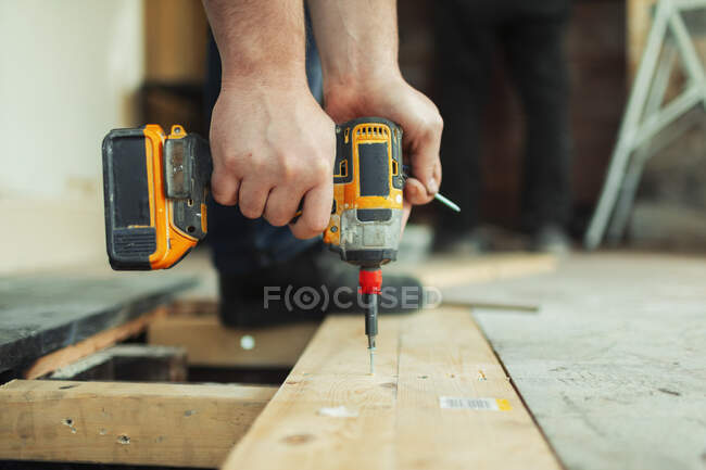 Close up construction worker using power drill installing floorboard — Stock Photo