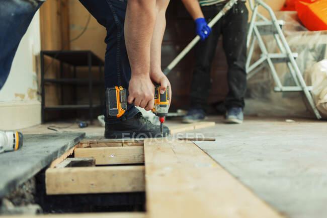Строитель с электрическим дриллером монтирует плиты пола на стройплощадке — стоковое фото