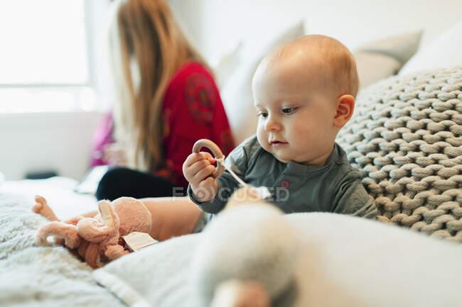 Niedliche neugierige Baby-Mädchen spielen mit Spielzeug auf dem Bett — Stockfoto