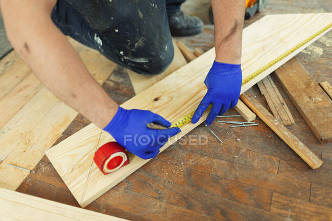 Construction worker measuring and marking floorboard — Stock Photo