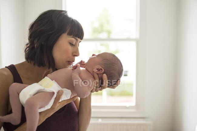 Madre cariñosa sosteniendo al bebé recién nacido hijo - foto de stock