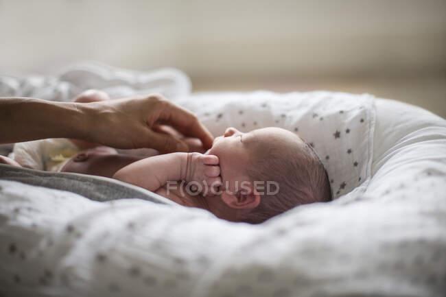 Madre toccando carino neonato figlio in culla — Foto stock