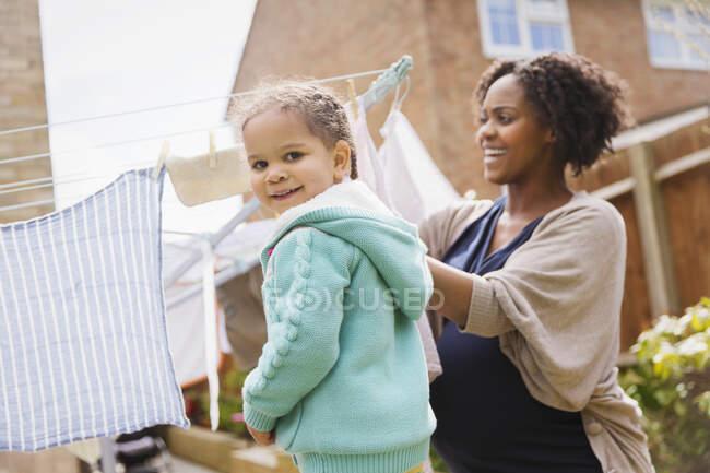 Porträt glückliches Mädchen hilft schwangerer Mutter Wäsche an Wäscheleine zu hängen — Stockfoto