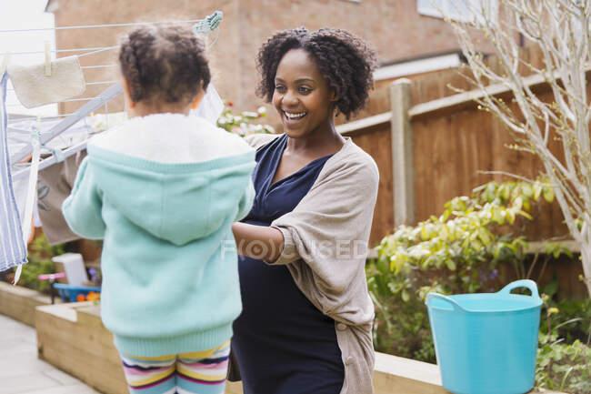 Счастливая беременная мать и дочь висят на бельевой веревке — стоковое фото
