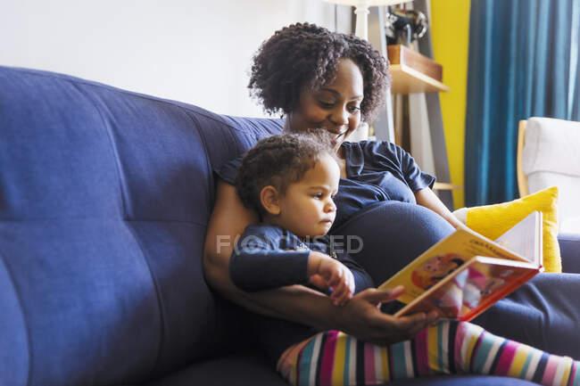 Schwangere Mutter und Tochter lesen Buch auf Sofa — Stockfoto