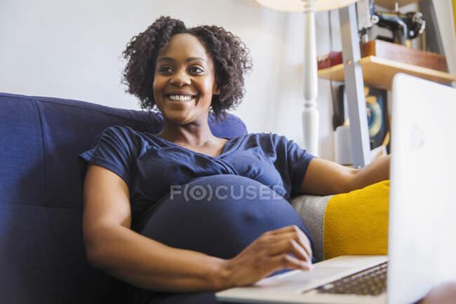 Счастливая беременная женщина с ноутбуком на диване — стоковое фото