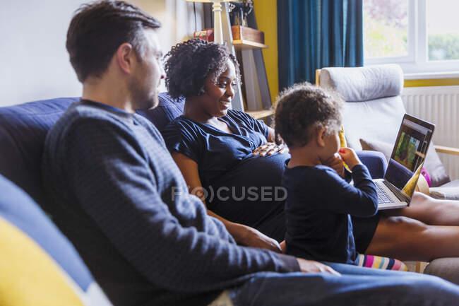 Мультикультурная семья с ноутбуком на диване — стоковое фото