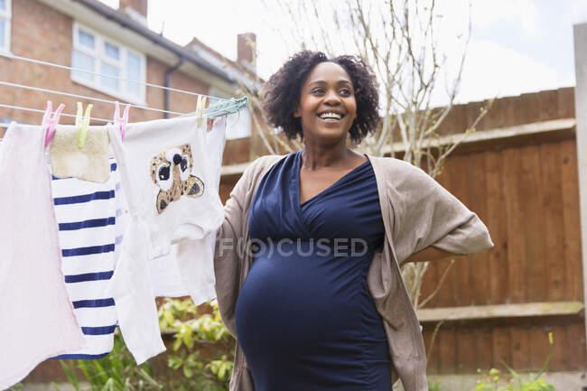 Счастливая беременная женщина висит на бельевой веревке в саду — стоковое фото