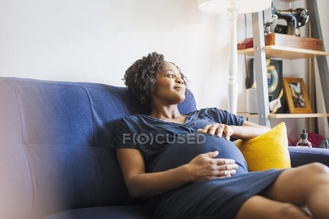 Serene pregnant woman relaxing on sofa — Stock Photo